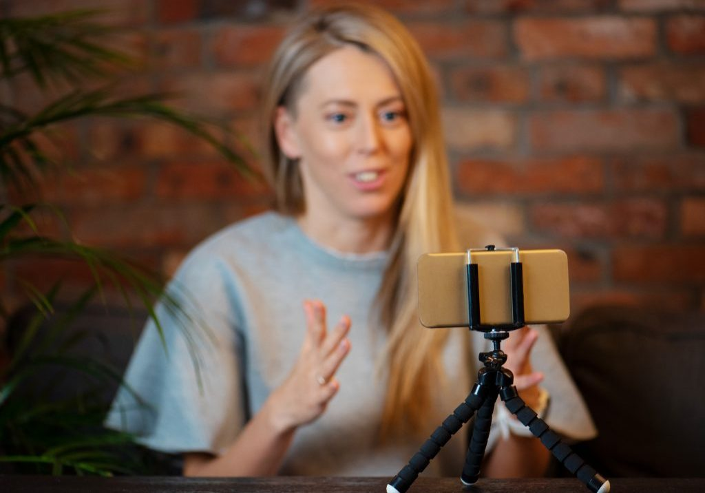 Woman recording video blog at home using mobile phone